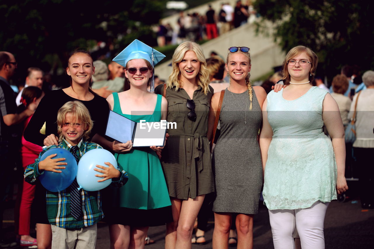 Portrait of smiling siblings during graduation ceremony
