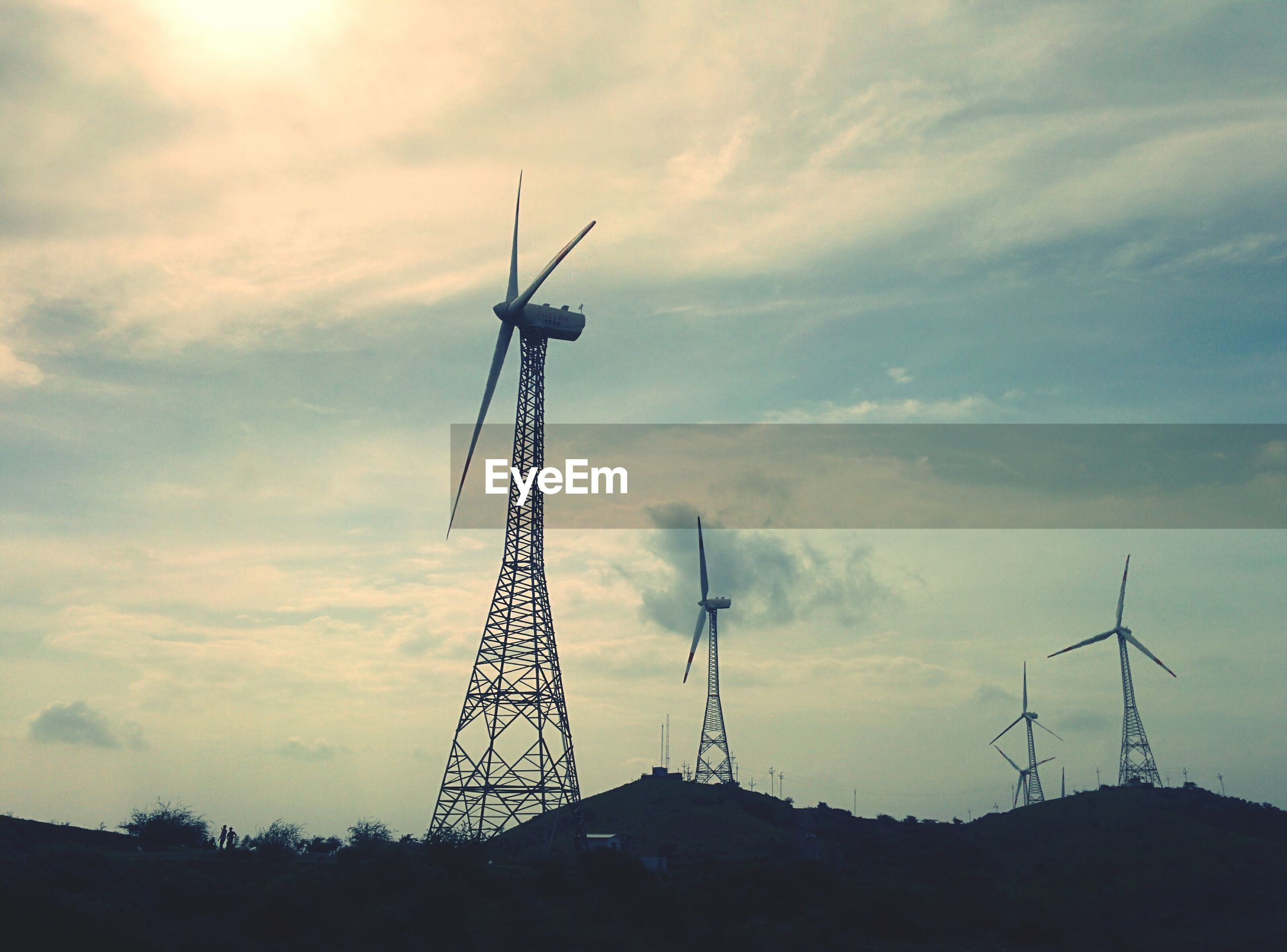 Low angle view of wind turbines against cloudy sky
