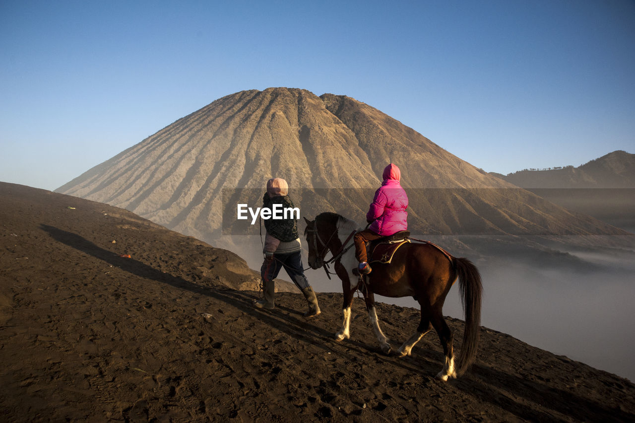 Rear View Of Person Riding Horse While Man Walking On Mountain Against Sky