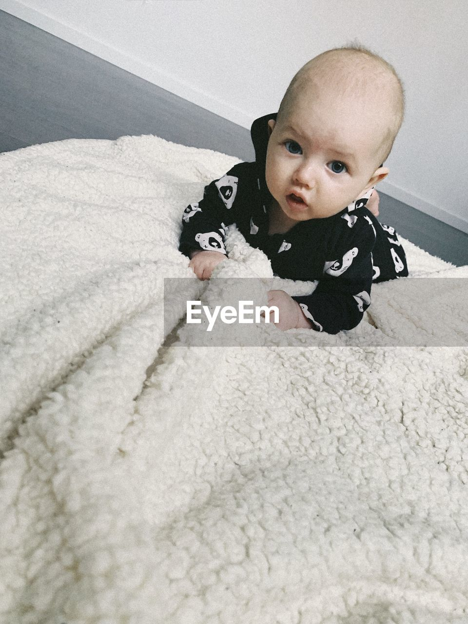 Portrait of cute baby on bed at home