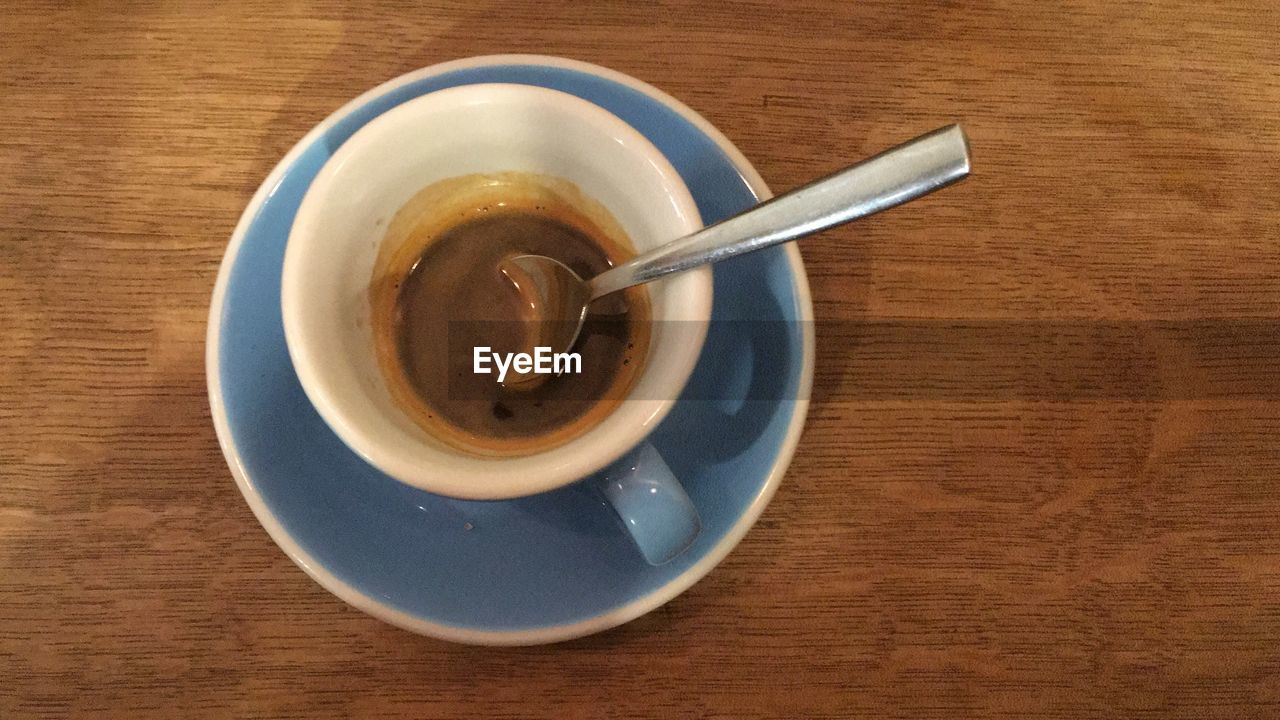 table, spoon, kitchen utensil, eating utensil, food and drink, still life, drink, wood - material, freshness, refreshment, indoors, directly above, cup, saucer, food, crockery, mug, coffee cup, coffee - drink, no people, teaspoon, wood grain, non-alcoholic beverage
