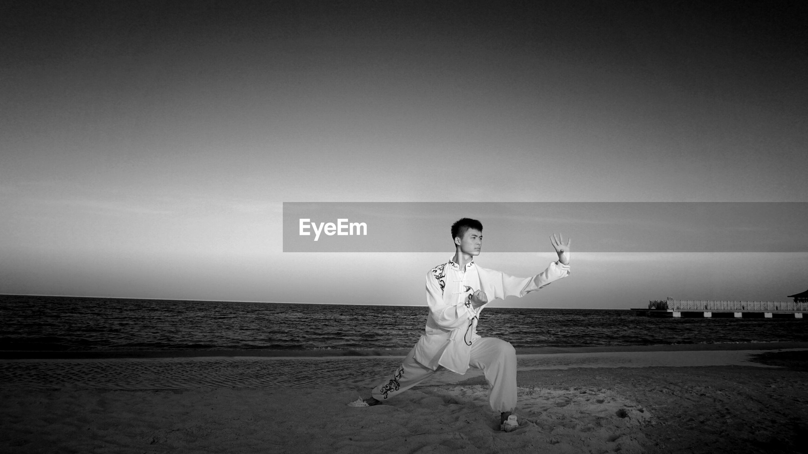 Full length of man practicing martial arts at beach against sky