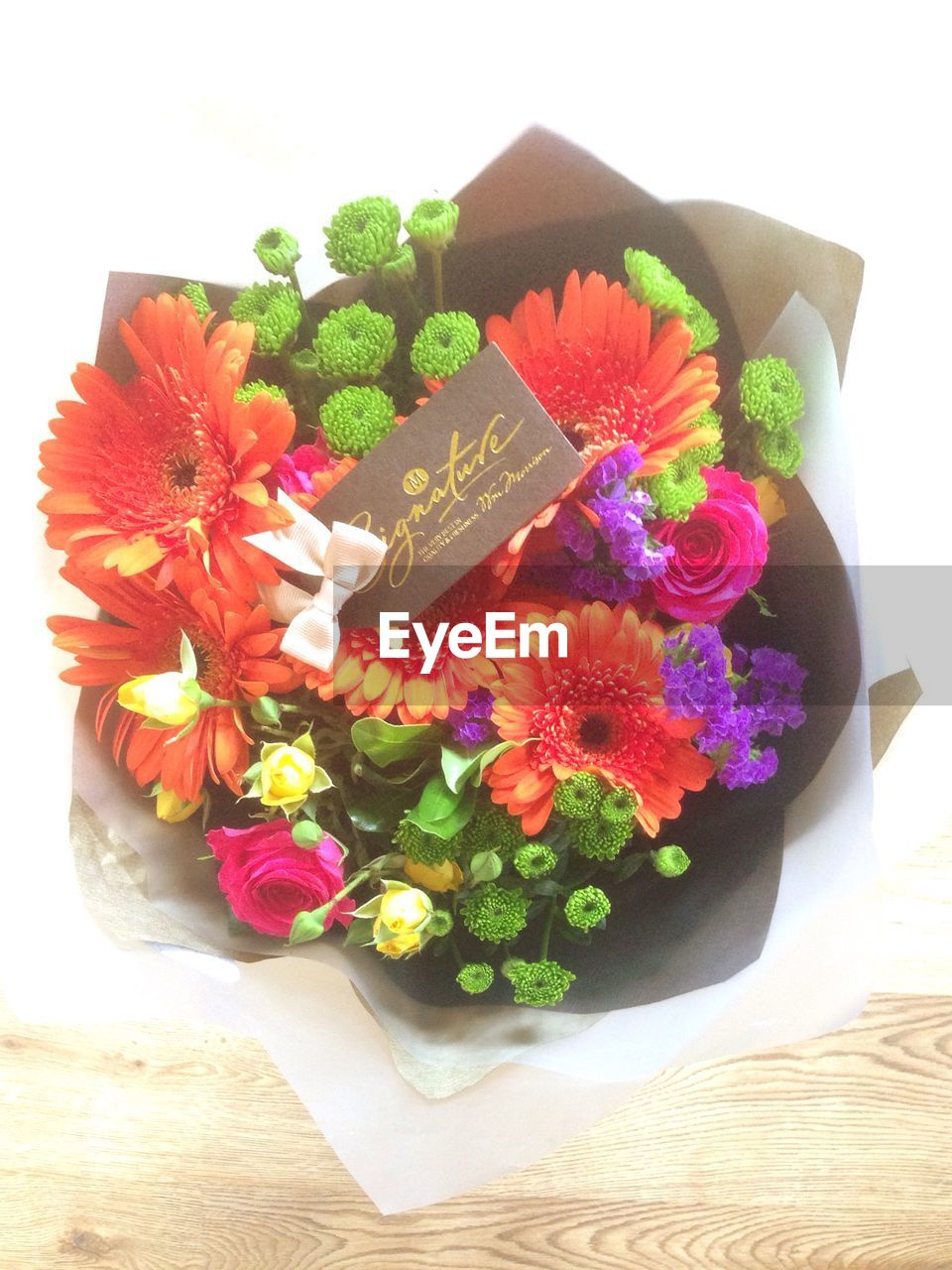 text, flower, high angle view, no people, white background, communication, table, freshness, indoors, close-up, food, multi colored, flower head, day
