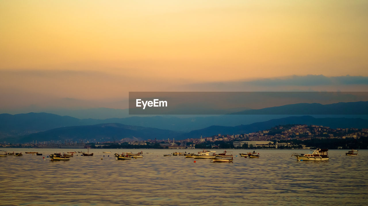 Boats sailing in river against sky at sunset