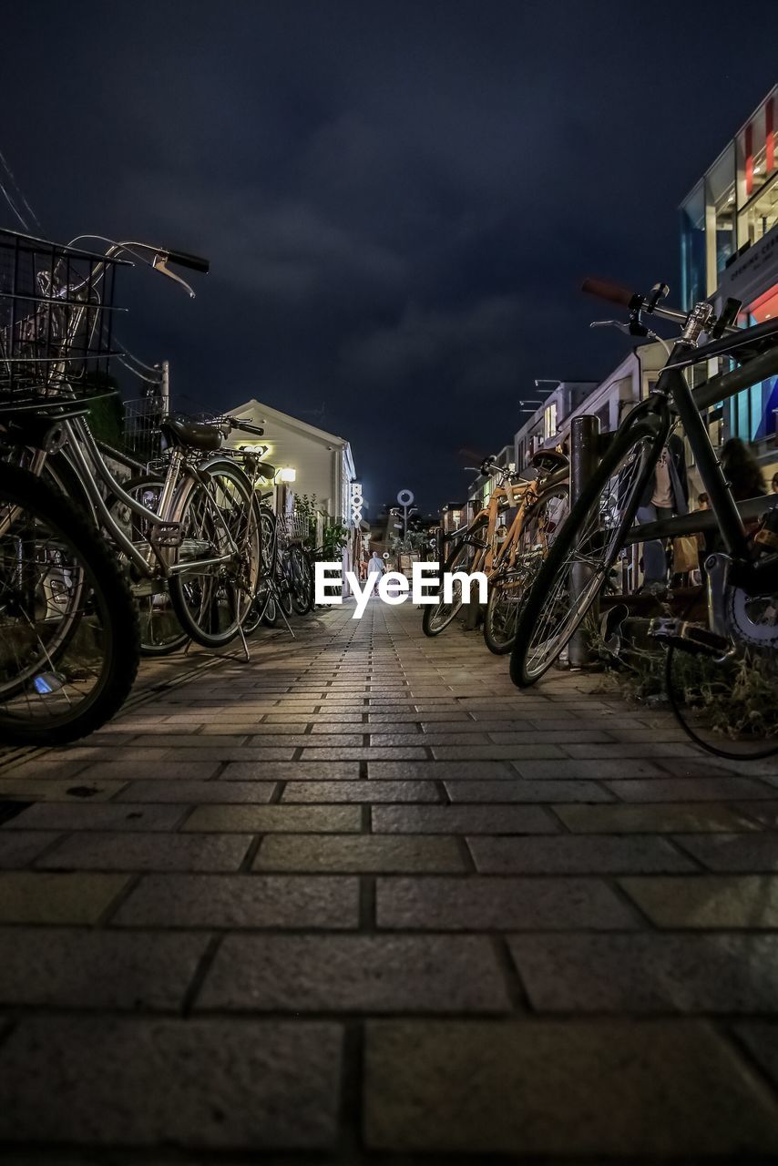transportation, bicycle, mode of transportation, the way forward, architecture, night, cloud - sky, sky, land vehicle, city, direction, street, built structure, building exterior, nature, stationary, outdoors, parking, incidental people, paving stone, wheel