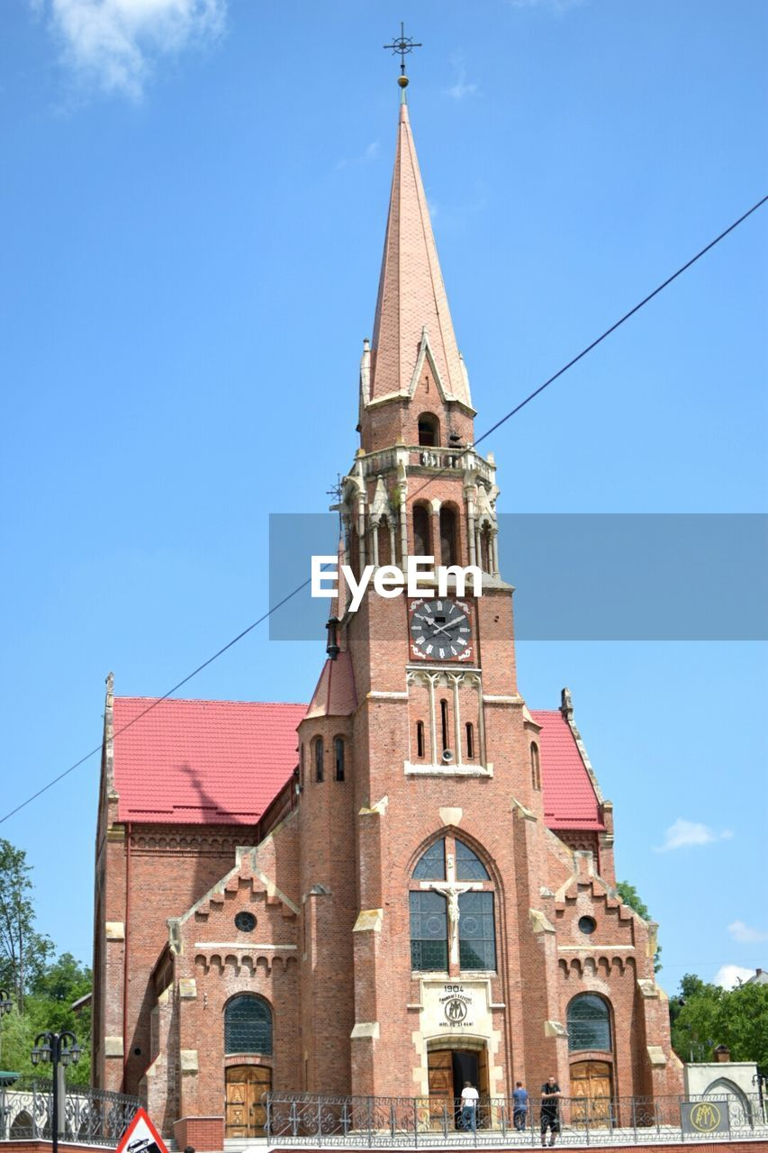religion, place of worship, architecture, spirituality, built structure, tower, building exterior, low angle view, history, bell tower, day, cross, blue, outdoors, no people, sky, clock tower, tree, clock