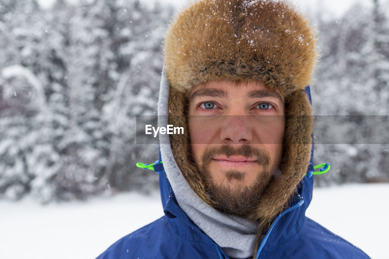 winter, cold temperature, snow, looking at camera, portrait, weather, warm clothing, real people, headshot, beard, one person, focus on foreground, mid adult men, day, outdoors, knit hat, front view, young men, leisure activity, nature, close-up, lifestyles, young adult, tree, people