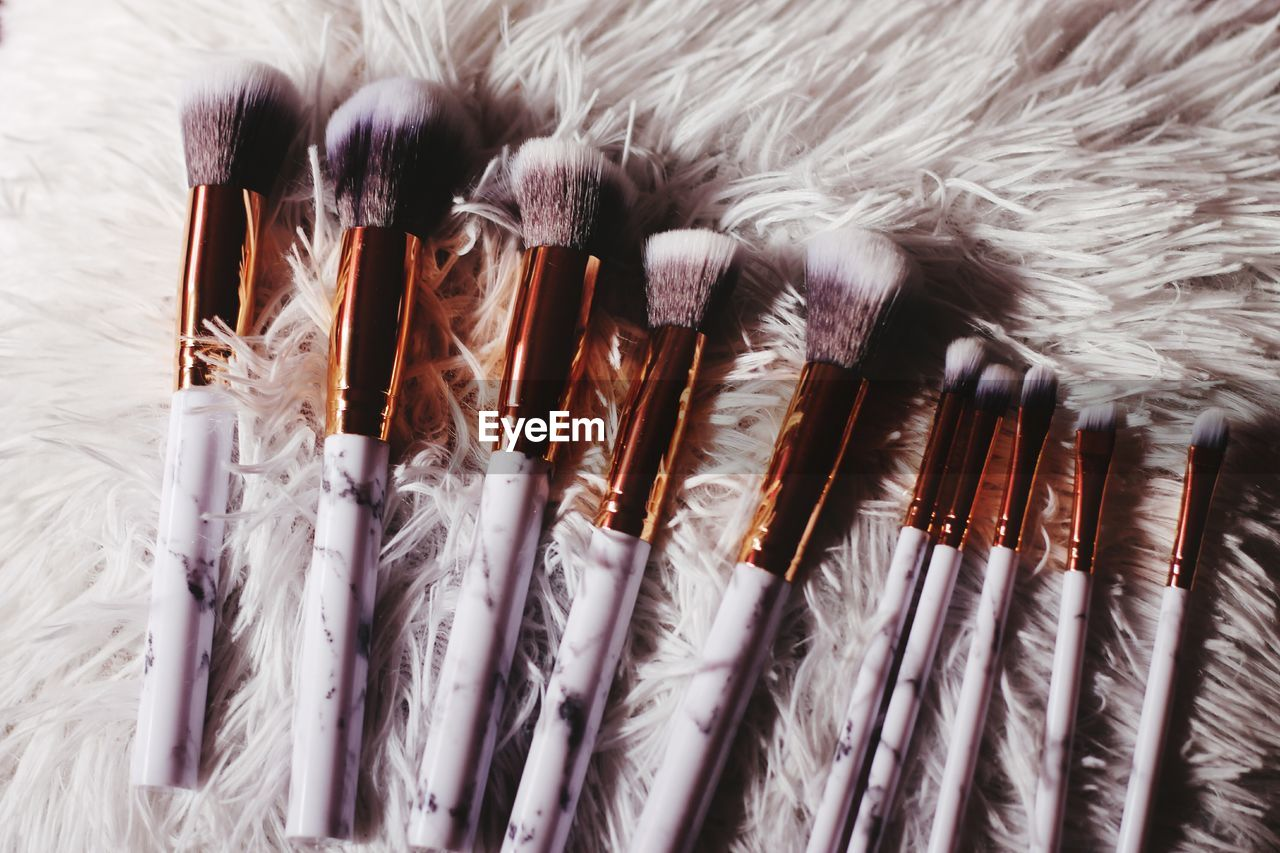 Close-Up Of Make-Up Brushes On Rug