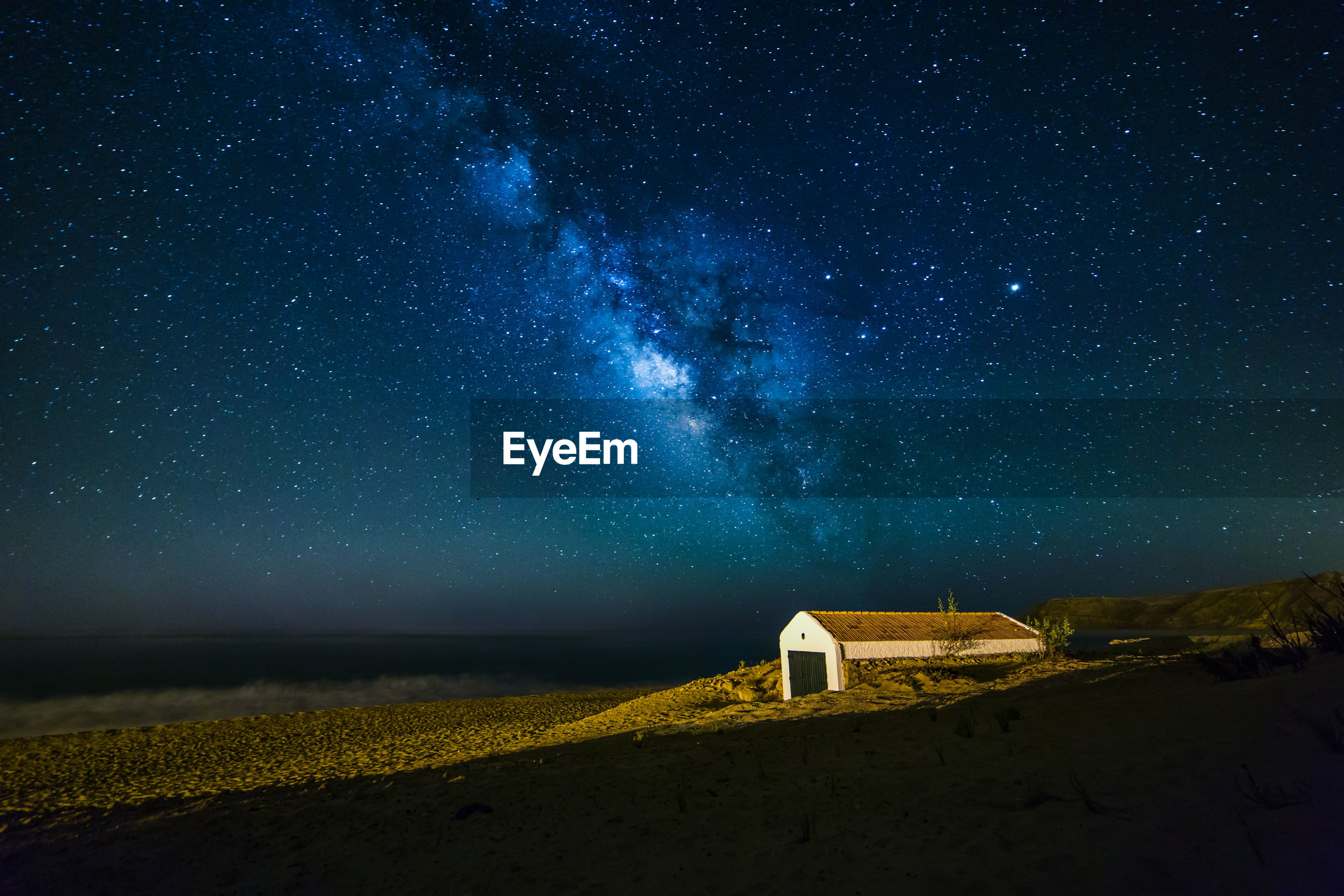 Building on sand by sea against milky way in sky at night