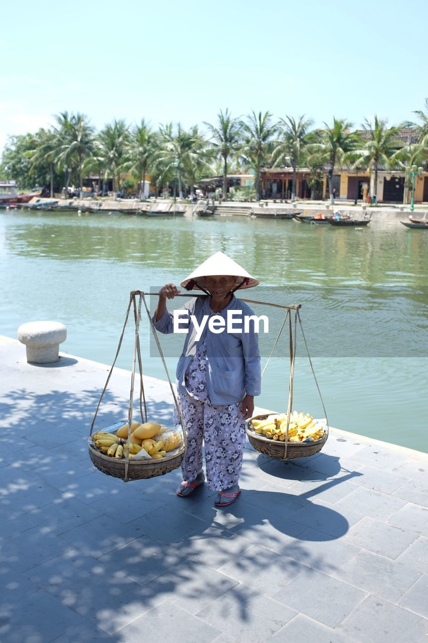 real people, water, one person, hat, outdoors, asian style conical hat, nautical vessel, day, full length, transportation, casual clothing, leisure activity, lifestyles, holding, sitting, nature, oar, tree, food, beauty in nature, people