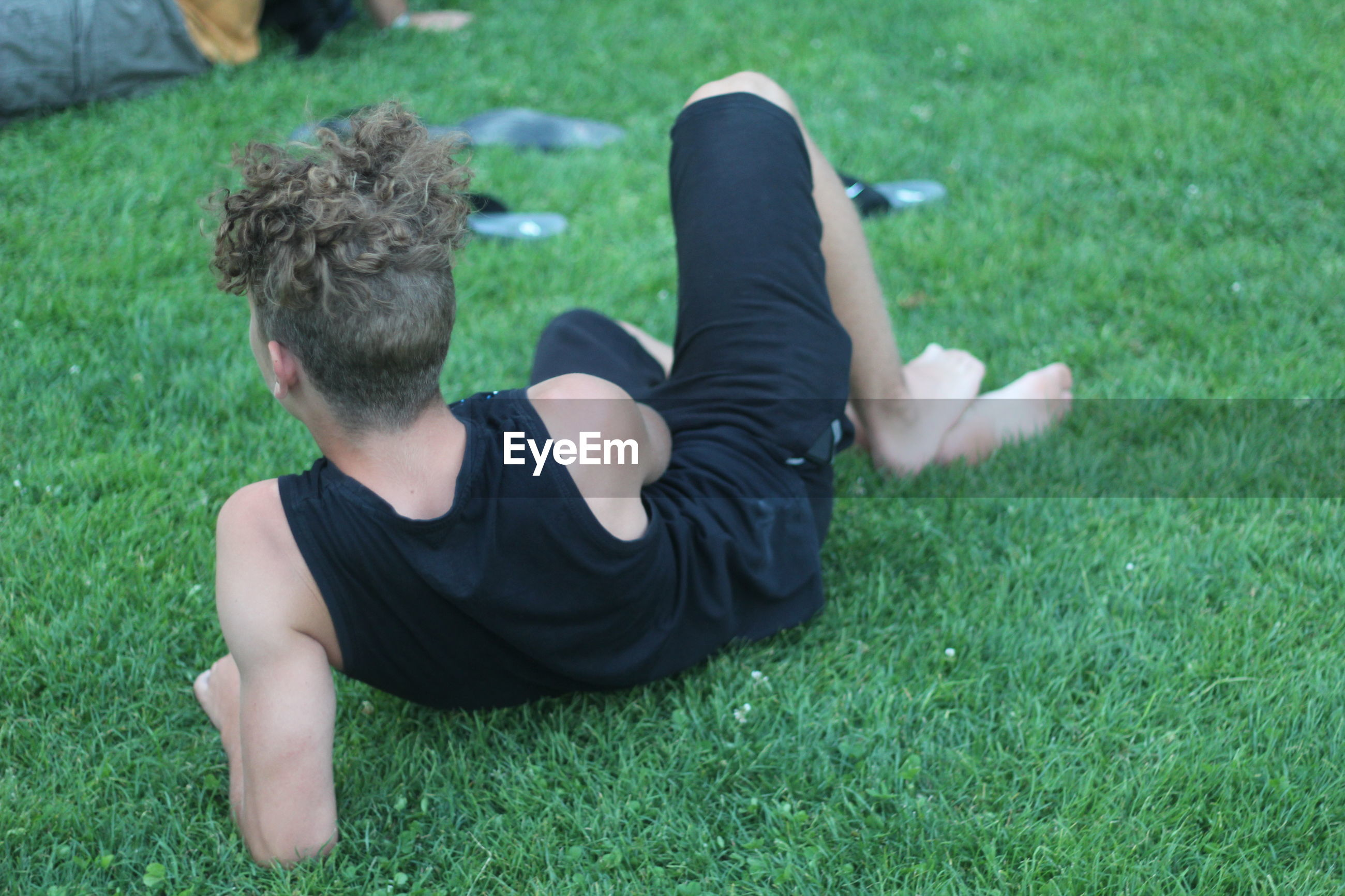 Rear view of teenage boy relaxing on grassy field at park