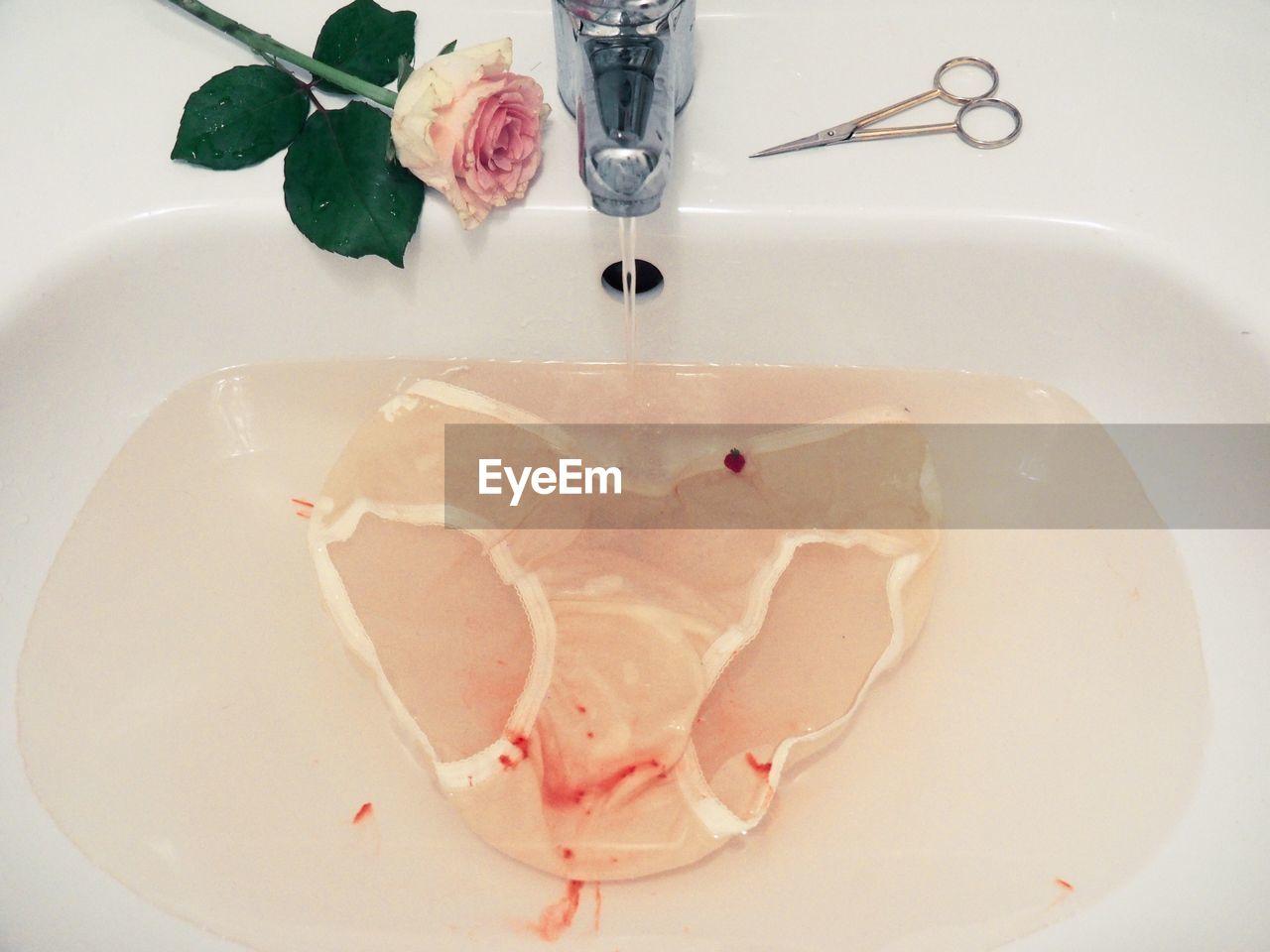 Stained underwear under running water in sink