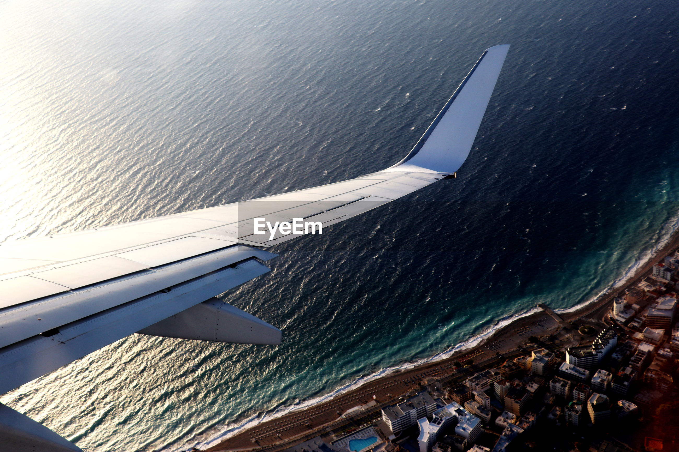 AERIAL VIEW OF SEA AND AIRPLANE FLYING OVER BOAT