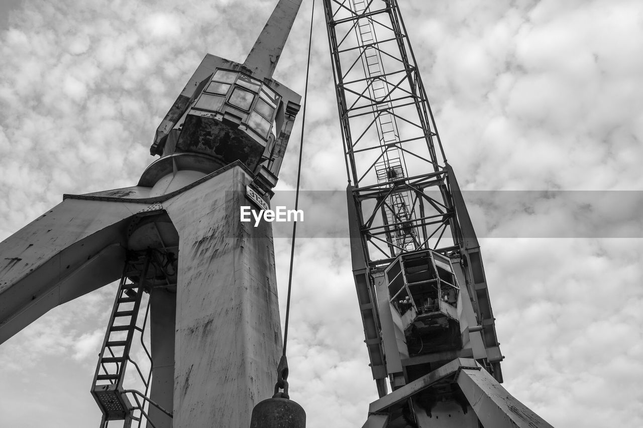 sky, cloud - sky, industry, low angle view, construction industry, built structure, day, nature, architecture, metal, crane - construction machinery, machinery, outdoors, tall - high, no people, development, fuel and power generation, construction site, construction machinery