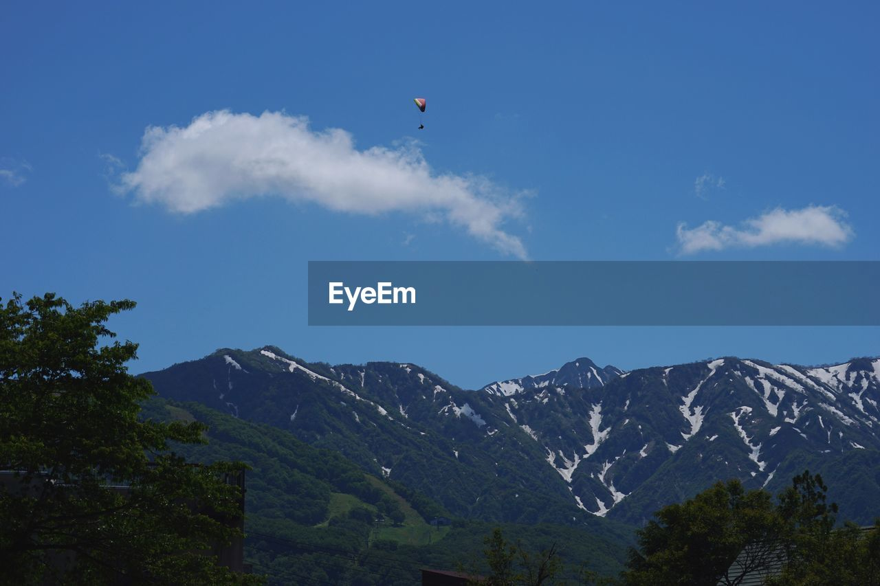 mountain, sky, beauty in nature, scenics - nature, mountain range, tranquil scene, cloud - sky, tranquility, flying, nature, non-urban scene, low angle view, day, mid-air, paragliding, tree, outdoors, no people, blue, idyllic, mountain peak, snowcapped mountain