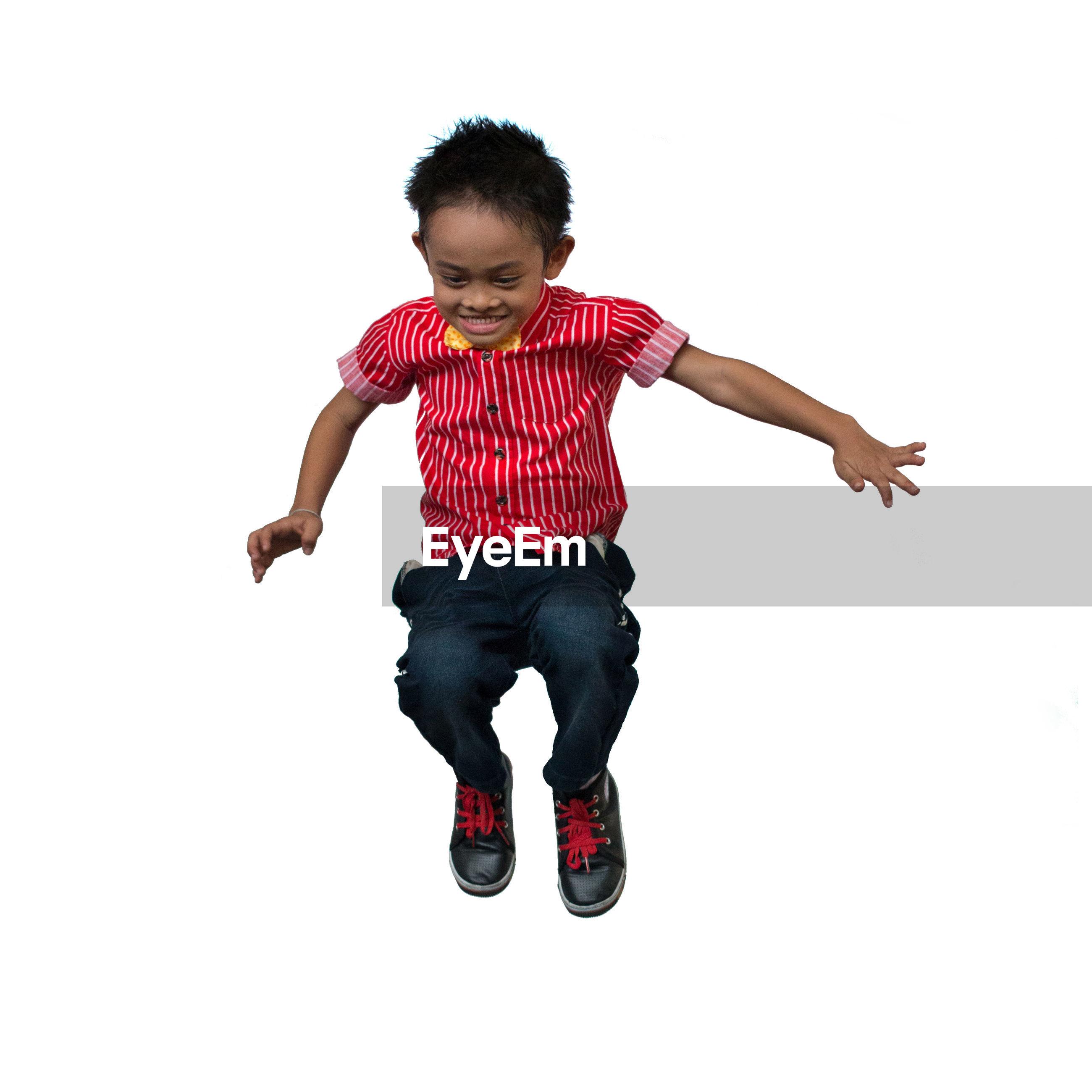 Full length of boy jumping against white background
