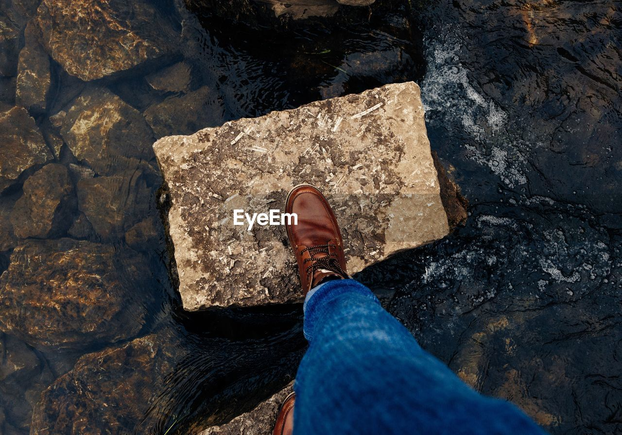Low Section Of Person Wearing Shoe While Standing On Rock Amidst Water