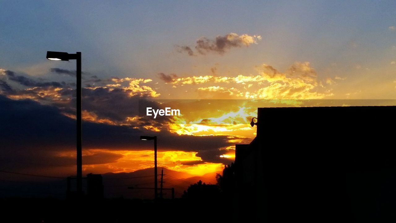 sunset, silhouette, cloud - sky, sky, dramatic sky, nature, orange color, no people, beauty in nature, outdoors, low angle view, scenics, yellow, built structure