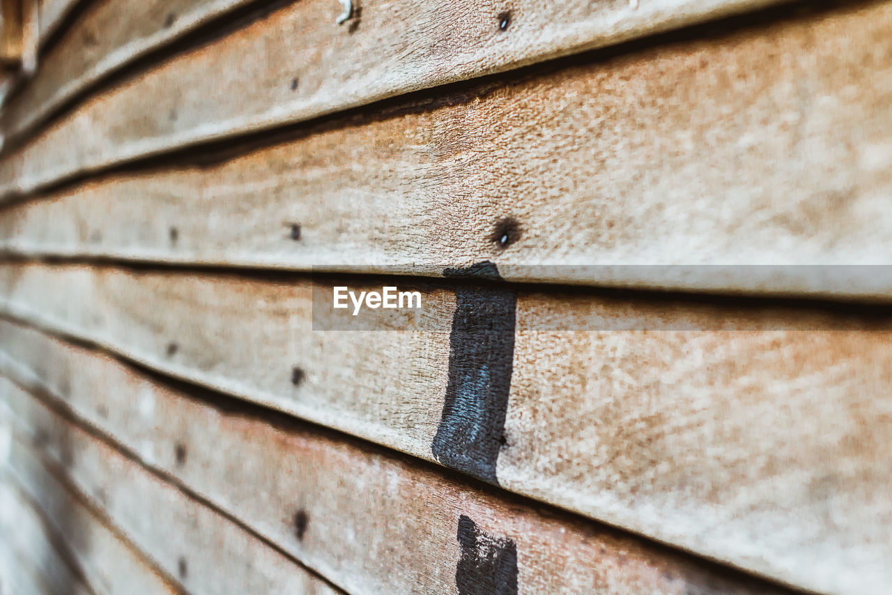full frame, no people, wood - material, close-up, backgrounds, pattern, textured, wall - building feature, day, metal, built structure, outdoors, selective focus, rough, brown, architecture, focus on foreground, wall, repetition, plank