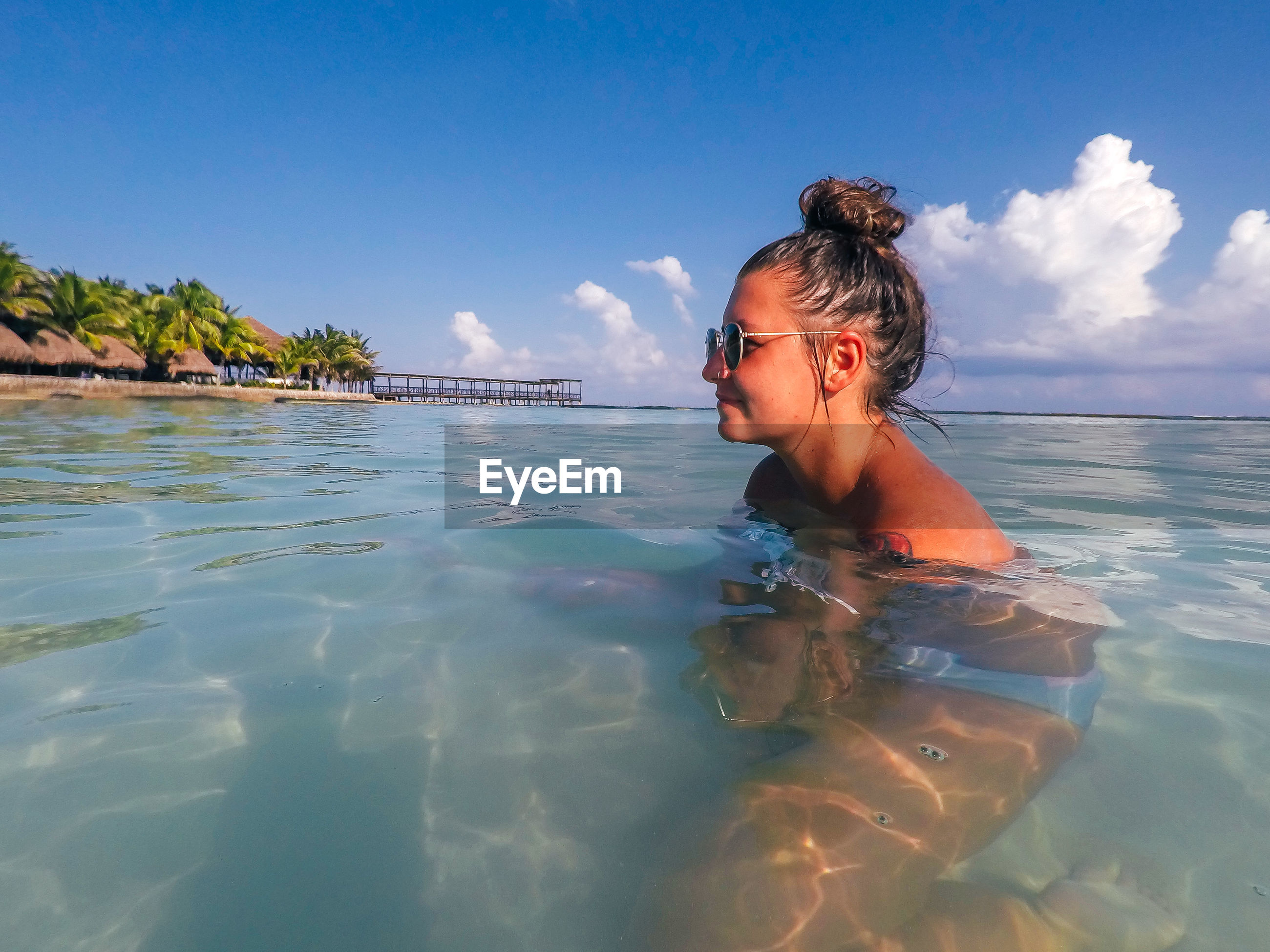 Side view of smiling young woman swimming in sea against blue sky