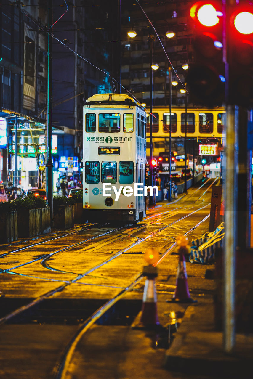 illuminated, transportation, mode of transportation, night, track, railroad track, architecture, rail transportation, city, public transportation, built structure, land vehicle, building exterior, street, cable car, no people, motion, outdoors, train, selective focus