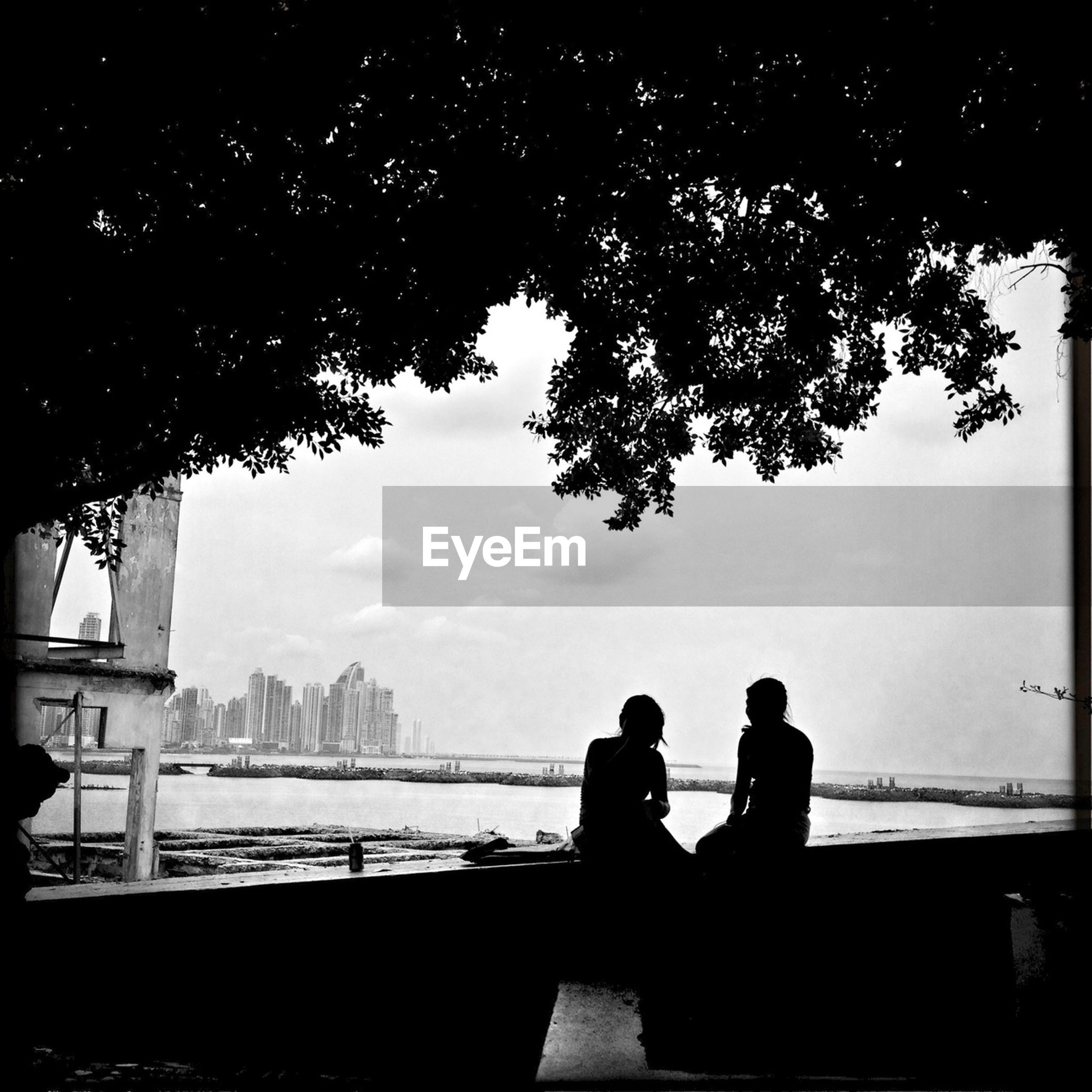 Silhouette couple overlooking calm river