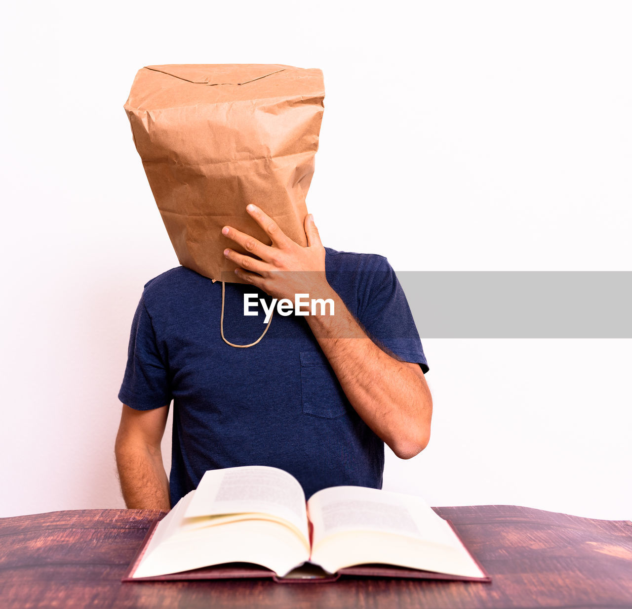 LOW SECTION OF PERSON ON BOOK AGAINST WHITE BACKGROUND