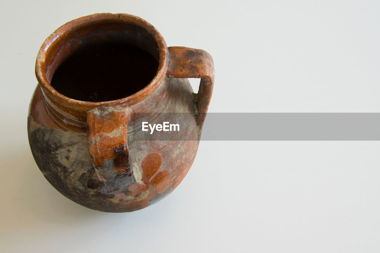 studio shot, still life, white background, indoors, copy space, single object, cup, close-up, no people, old, mug, metal, food and drink, rusty, handle, drink, coffee, refreshment, high angle view, coffee cup
