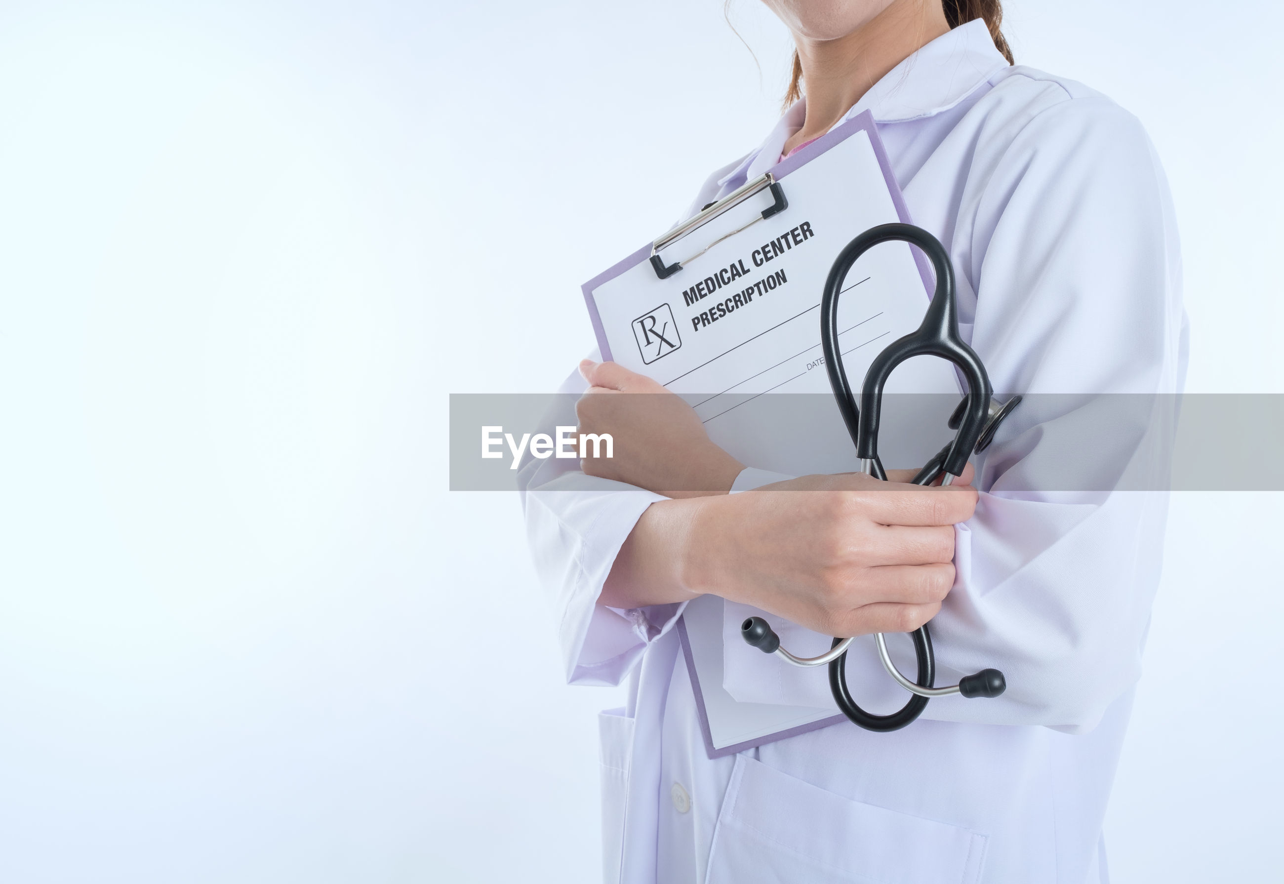 Midsection of female doctor with clipboard and stethoscope standing against white background