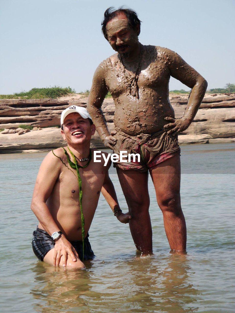 Happy Men Enjoying Mud Bath In Pond Against Sky