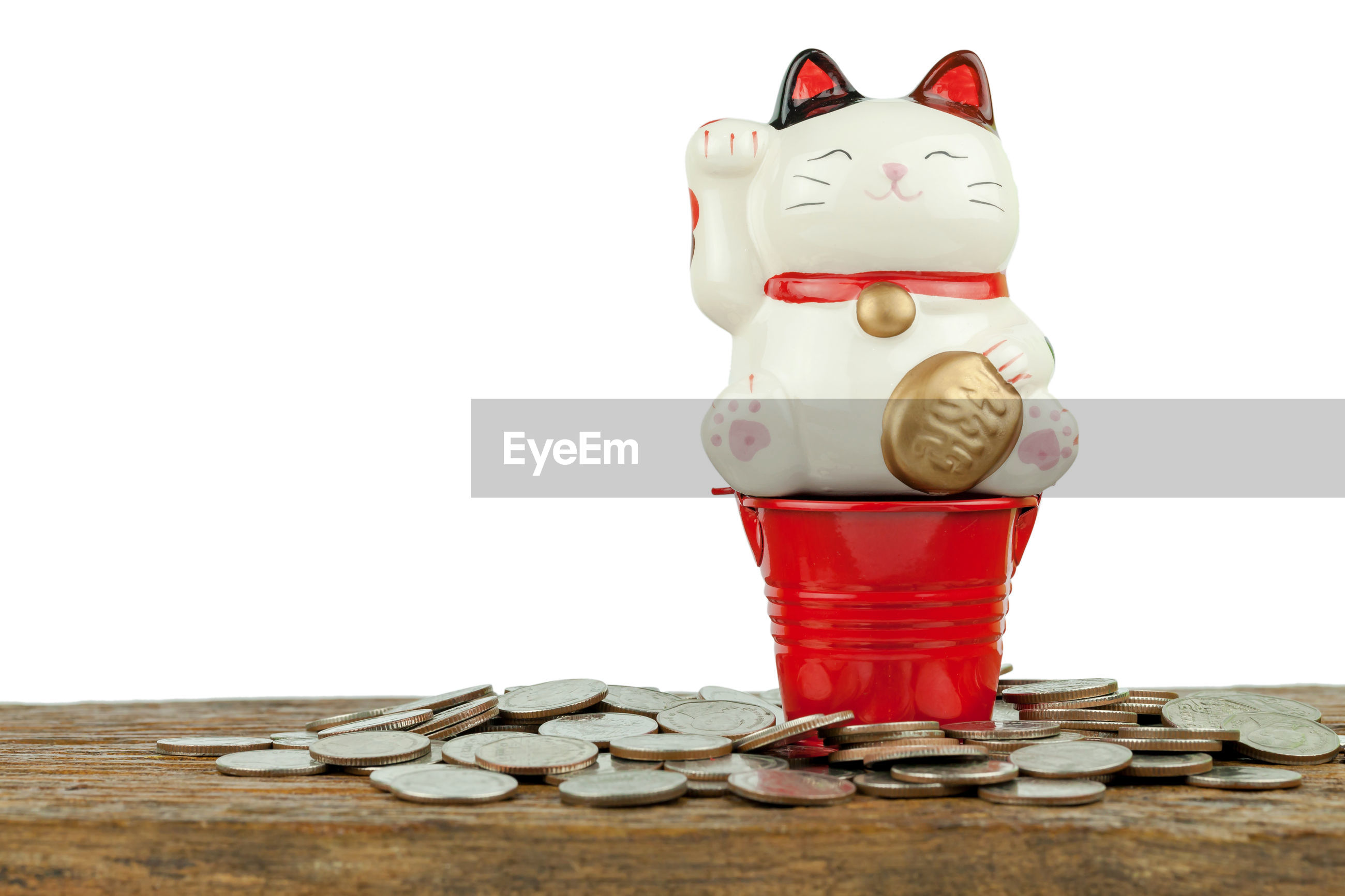 Close-up of maneki-neko and coins on table against white background