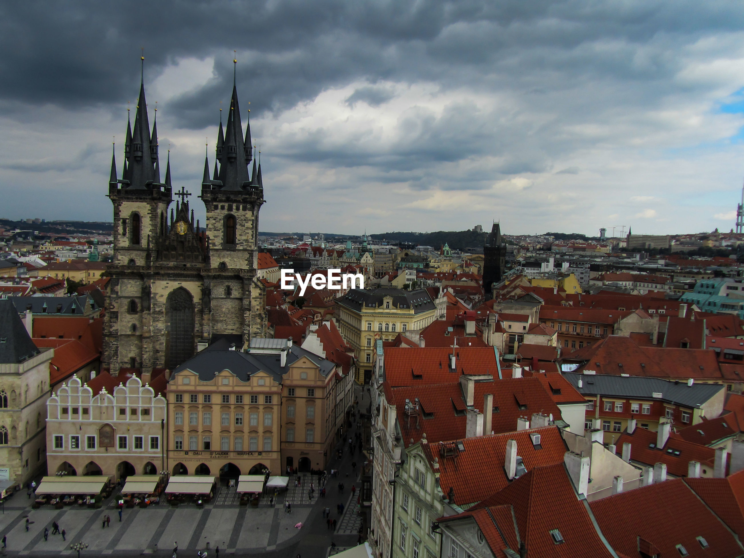 High angle view of tyn church and cityscape against cloudy sky