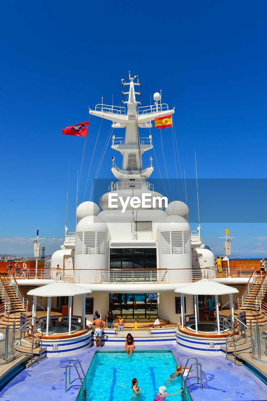 nautical vessel, blue, boat, clear sky, mode of transport, flag, transportation, moored, day, outdoors, water, swimming pool, no people, vacations, yacht, building exterior, architecture, nature