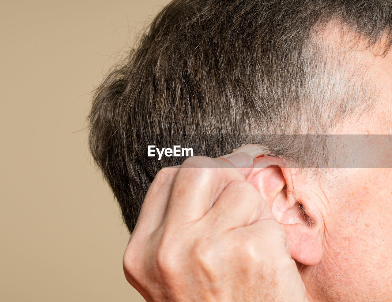 Close-Up Of Senior Man Holding Hearing Aid Against Beige Background