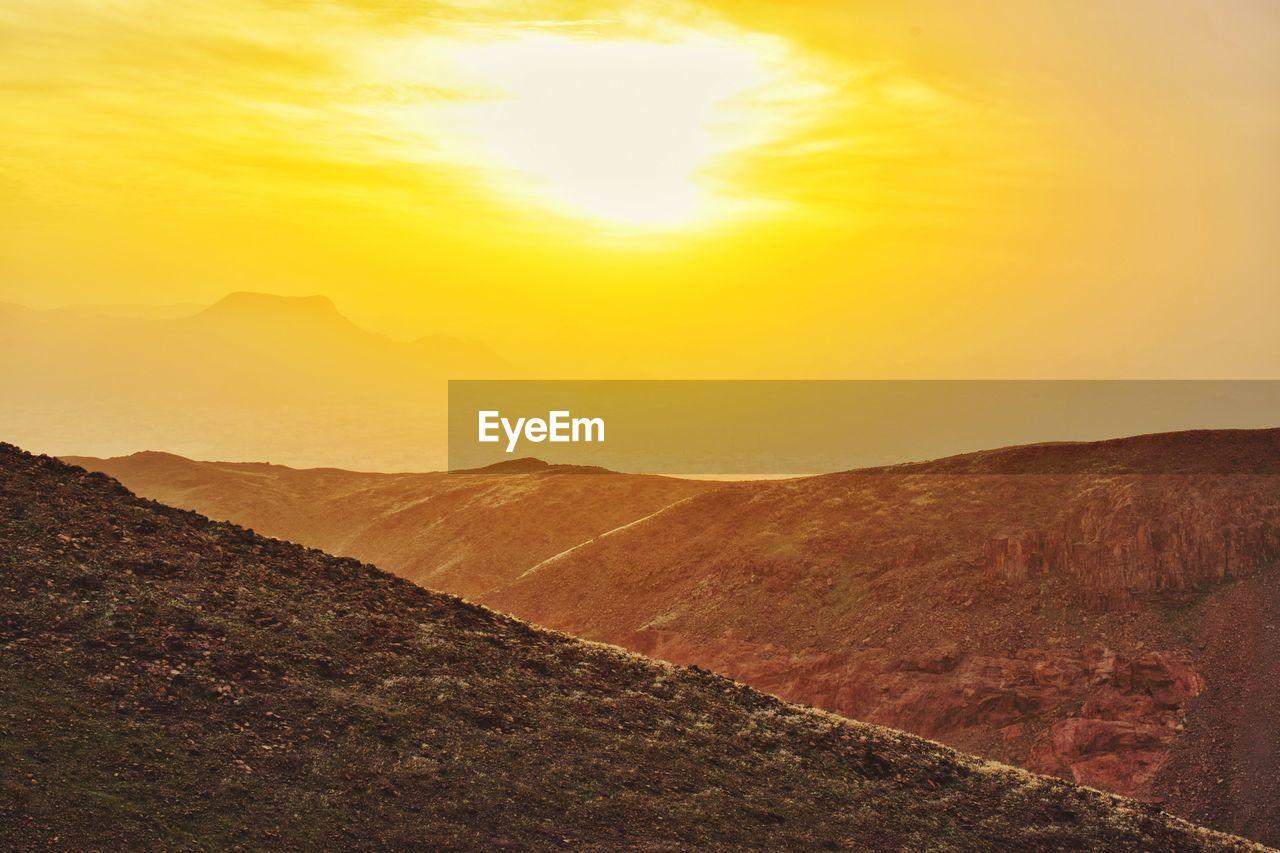 sky, mountain, environment, tranquility, beauty in nature, scenics - nature, sunset, tranquil scene, landscape, nature, mountain range, non-urban scene, sunlight, no people, land, idyllic, cloud - sky, orange color, sun, outdoors, bright