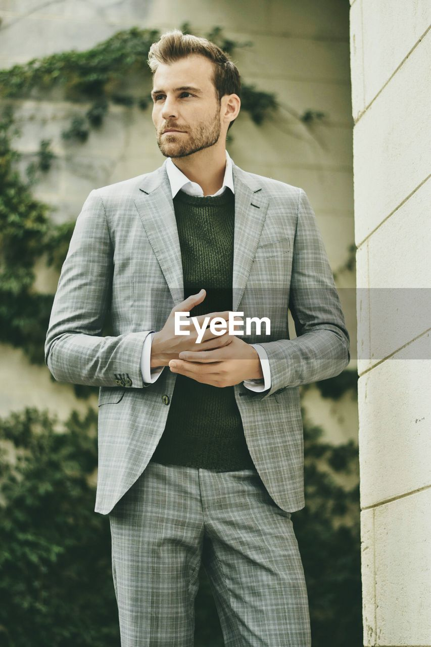 Young Businessman Looking Away While Standing By Wall