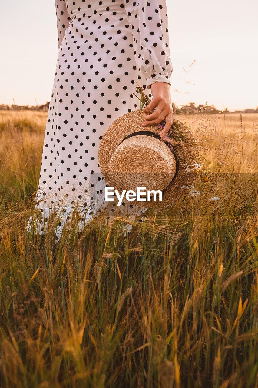 WOMAN HOLDING HAT IN FIELD