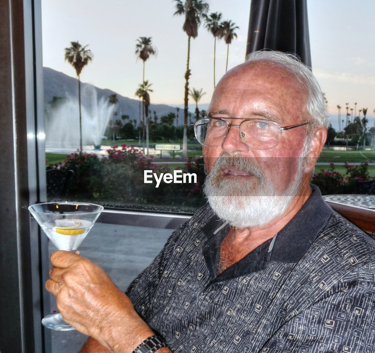 Portrait of mature man holding martini glass by window
