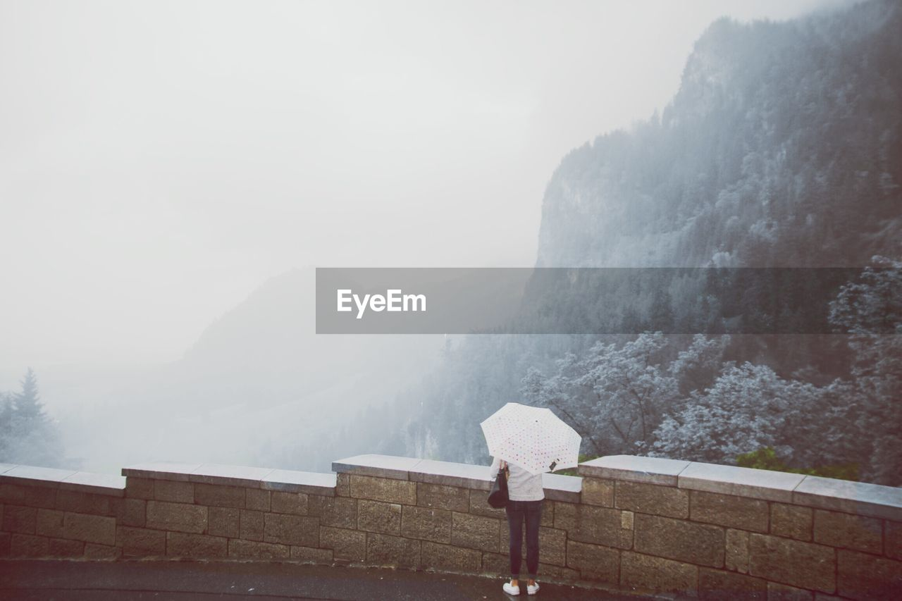 one person, real people, mountain, fog, rear view, nature, standing, women, adult, sky, day, umbrella, scenics - nature, beauty in nature, lifestyles, wall, leisure activity, rain, outdoors, mountain range