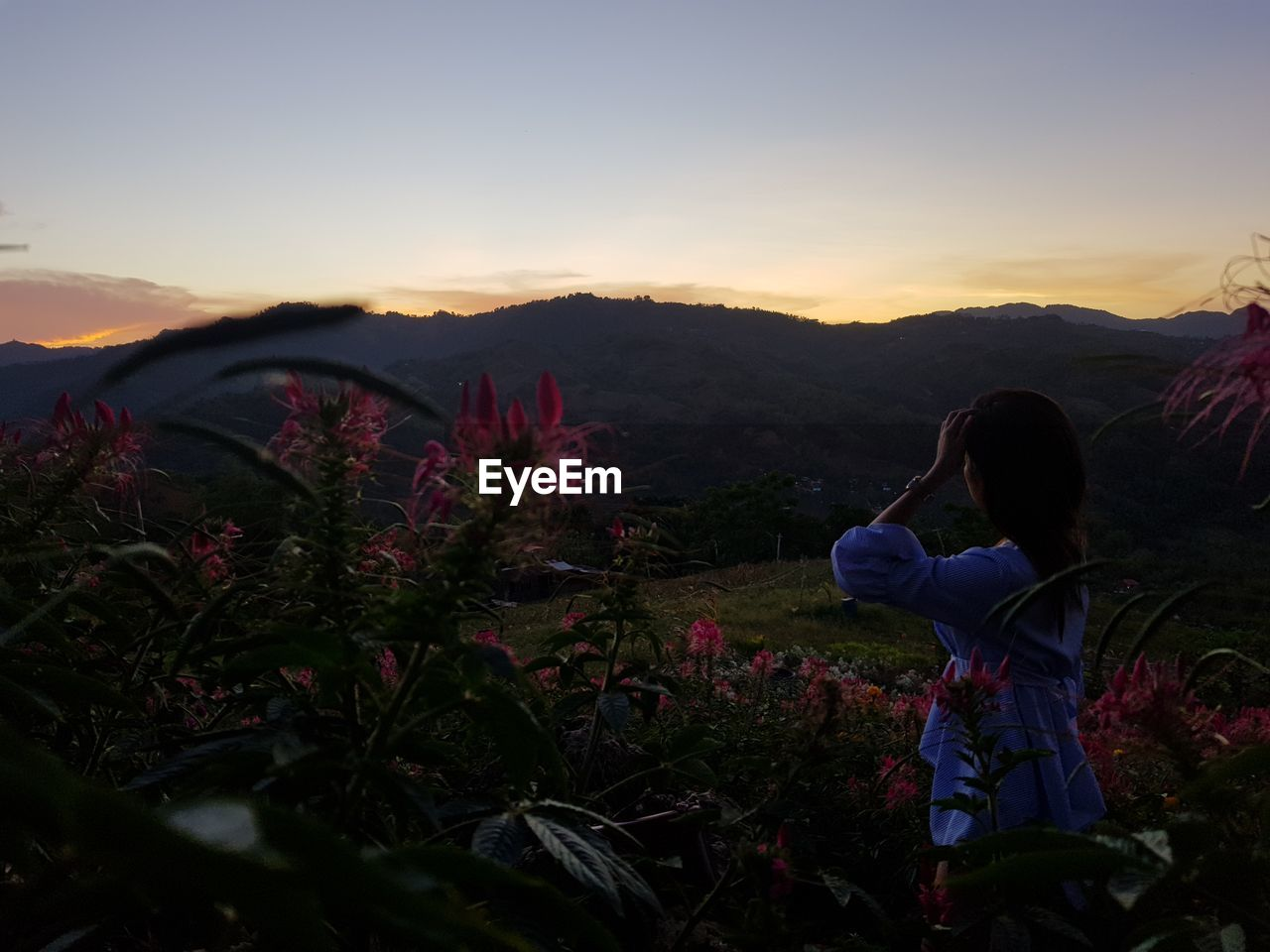 Side view of woman looking at mountains against sky during sunset