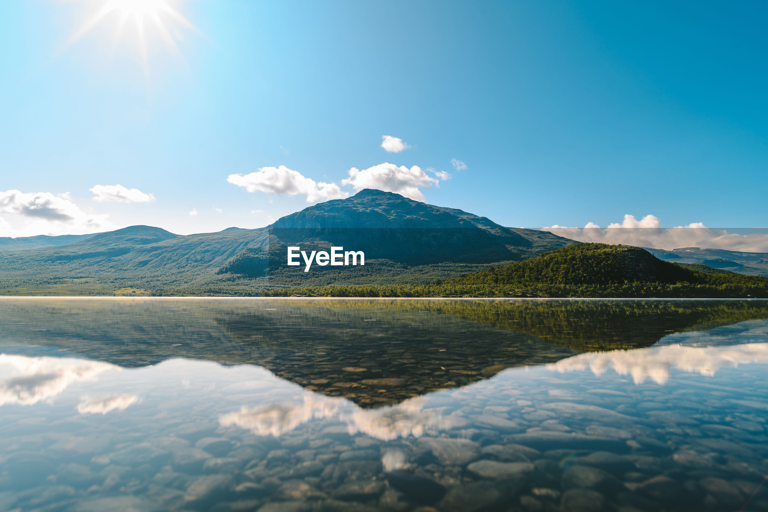 View of lake by mountain against sky
