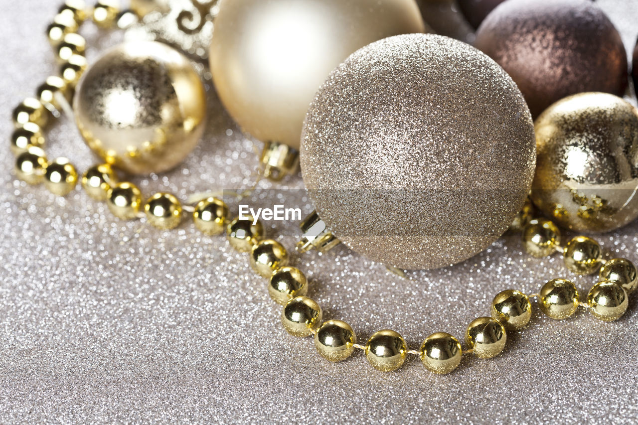 jewelry, gold colored, necklace, wealth, close-up, no people, pearl jewelry, luxury, indoors, shiny, gold, studio shot, still life, metal, bead, fashion, focus on foreground, personal accessory, high angle view, earring, expense, precious gem, silver colored