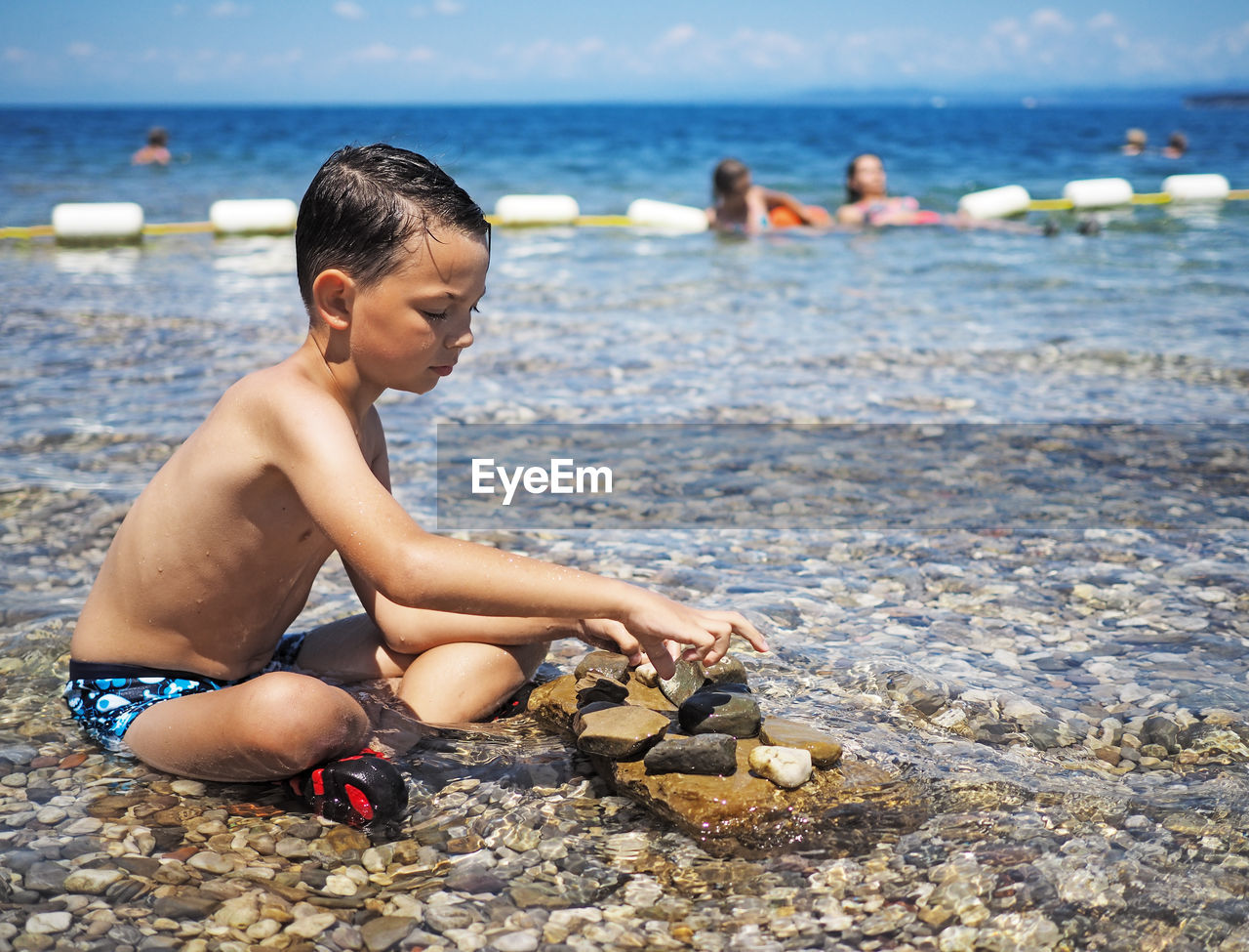 Full Length Of Shirtless Boy Playing With Stones On Shore At Beach