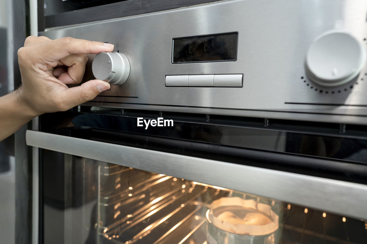 human hand, hand, human body part, one person, appliance, oven, indoors, lifestyles, holding, real people, domestic room, kitchen, unrecognizable person, technology, focus on foreground, home, domestic kitchen, metal, body part, finger, push button, human limb