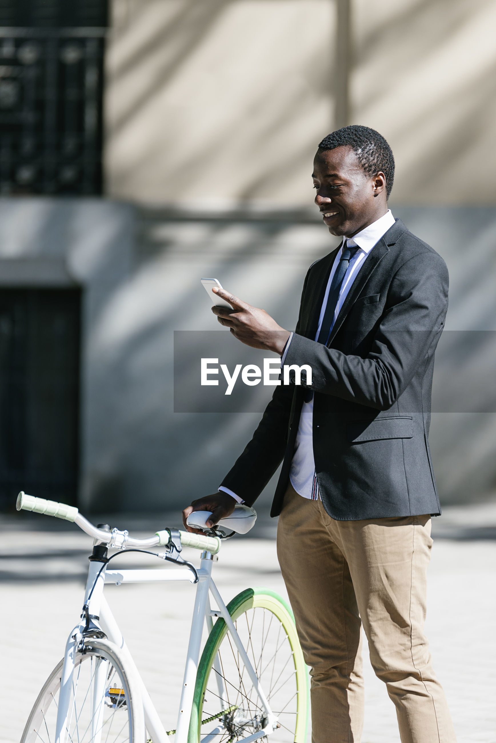 Side view of businessman using phone while standing on road with bicycle