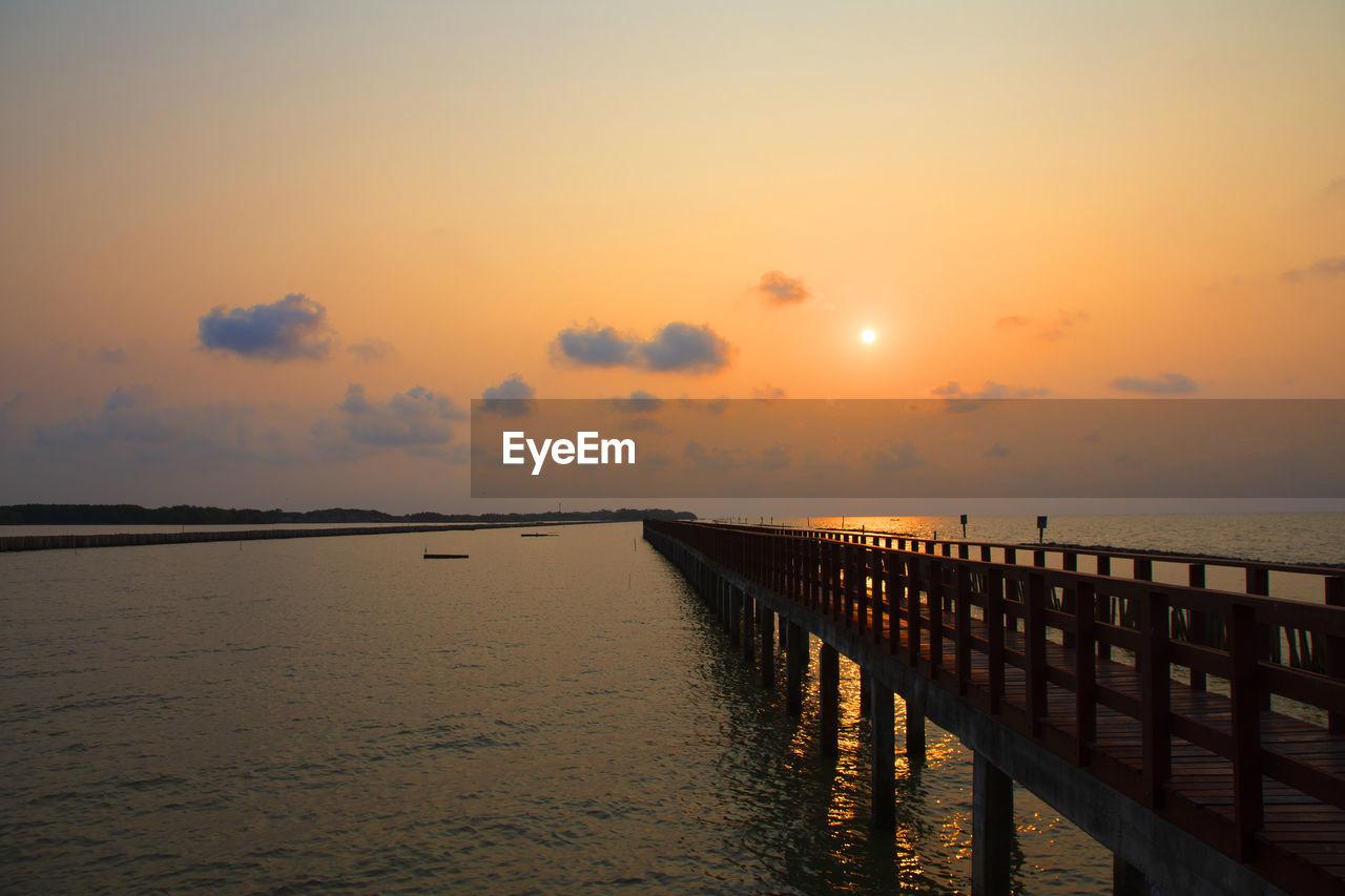 sunset, sky, water, sea, scenics - nature, beauty in nature, tranquility, tranquil scene, orange color, sun, horizon, nature, cloud - sky, idyllic, horizon over water, pier, railing, no people, non-urban scene, outdoors, wooden post