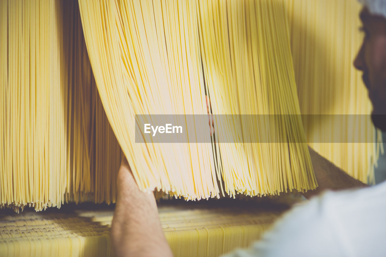Cropped Image Of Person Checking Spaghetti Drying In Factory