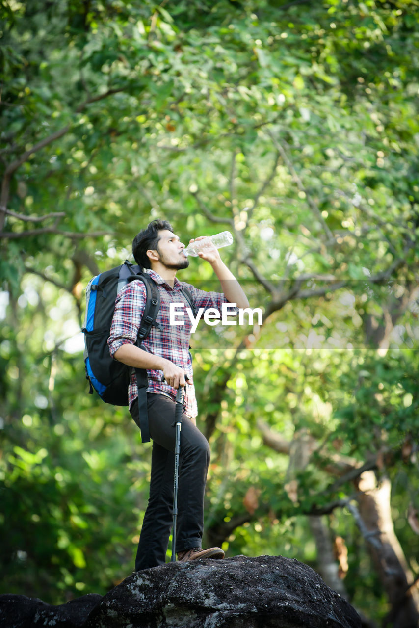 Young Man Drinking Water While Standing On Rock By Trees In Forest
