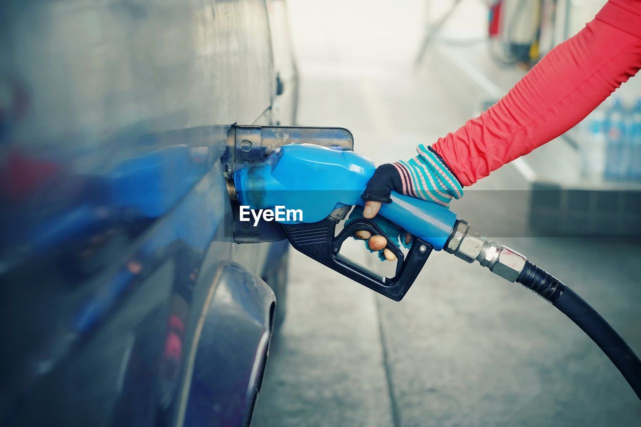 Close-up of person refueling car at gas station