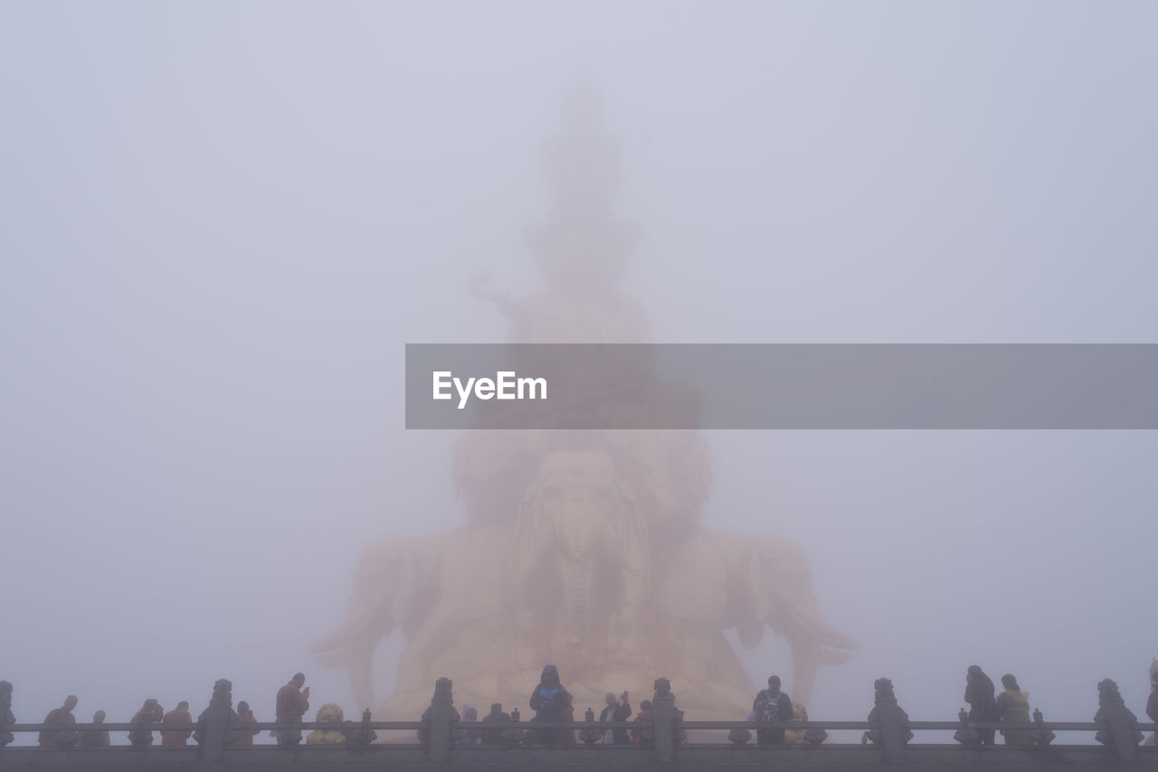 large group of people, real people, women, history, lifestyles, tourism, men, religion, sky, leisure activity, fog, statue, spirituality, travel destinations, ancient, outdoors, day, low angle view, sculpture, built structure, architecture, nature, crowd, ancient civilization, people